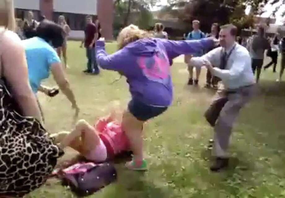 Screen grab from the Shenendehowa schoolyard brawl on YouTube. In the video, one girl -- wearing a hoodie with a peace sign on it -- is shown walking over to another girl who is sitting on the grass. The attacking girl kicks and punches the victim, who tries to protect herself from the blows. A woman tries to stop the fight, only to be ignored. Assistant Principal Matthew Heckman then appears suddenly in the video, shoving the attacking girl to the ground.
