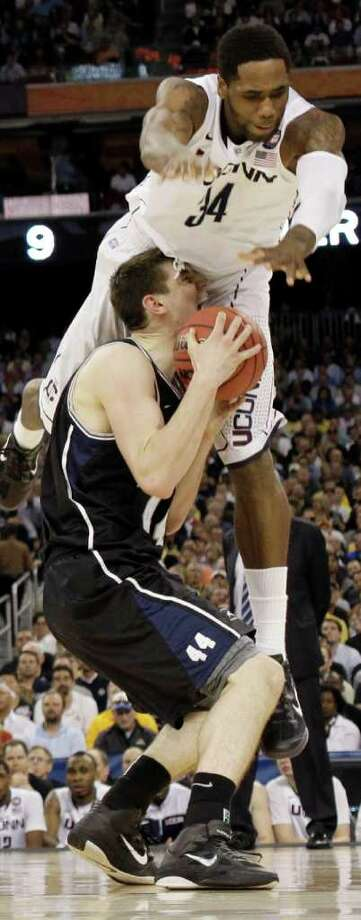 Connecticut's Alex Oriakhi topples over  Butler's Andrew Smith during the first half of the men's NCAA Final Four college basketball championship game Monday, April 4, 2011, in Houston. (AP Photo/Eric Gay) Photo: AP