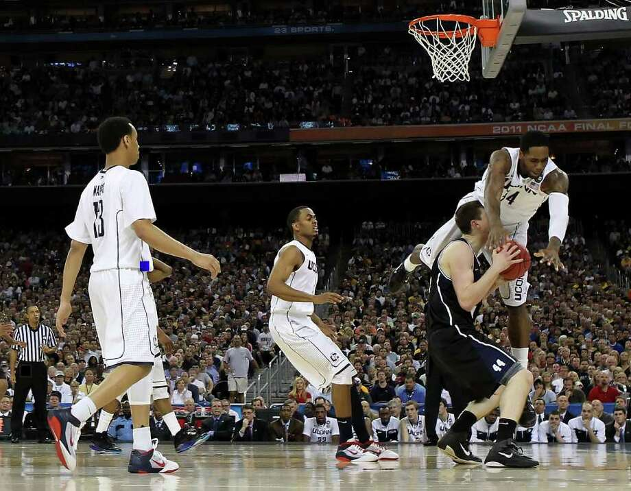 HOUSTON, TX - APRIL 04:  Alex Oriakhi #34 of the Connecticut Huskies goes to the court in front of Andrew Smith #44 of the Butler Bulldogs during the National Championship Game of the 2011 NCAA Division I Men's Basketball Tournament at Reliant Stadium on April 4, 2011 in Houston, Texas.  (Photo by Streeter Lecka/Getty Images) *** Local Caption *** Alex Oriakhi;Andrew Smith Photo: Streeter Lecka, Getty Images / 2011 Getty Images