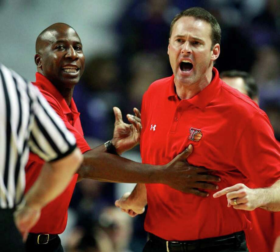 FILE - In a Jan. 15, 2011 file photo, Texas Tech coach Pat Knight, right, is held by assistant coach Stew Robinson after being called for a technical foul during the first half of an NCAA college basketball game against Kansas State, in Manhattan, Kan. Texas Tech has fired coach Pat Knight.  School spokesman Blayne Beal said Monday, March 7, 2011 that Knight will coach the Red Raiders at this week's Big 12 tournament and then will step down.  Knight is in his third year as head coach. He took over the program from his famous father, Bob Knight, midseason in February 2008.  (AP Photo/Orlin Wagner, File) Photo: Orlin Wagner, STF / AP2011