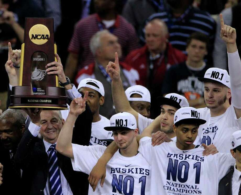 Connecticut coach Jim Calhoun holds the NCAA National Championship trophy with his University of Connecticut team as they celebrate their 53-41 win over Butler during the NCAA National Championship at Reliant Stadium on Monday, April 4, 2011, in Houston.  ( Brett Coomer / Houston Chronicle ) Photo: Brett Coomer, Houston Chronicle For The Connecticut Post / Houston Chronicle for the Connecticut Post