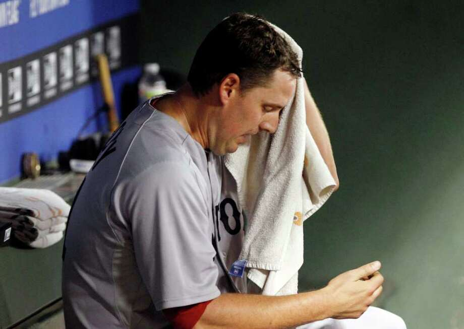 Boston Red Sox starting pitcher John Lackey sits in the dugout after he was pulled from the game in the fourth inning of the baseball game against the Texas Rangers in Arlington, Texas, Saturday, April 2, 2011.  (AP Photo/LM Otero) Photo: LM Otero