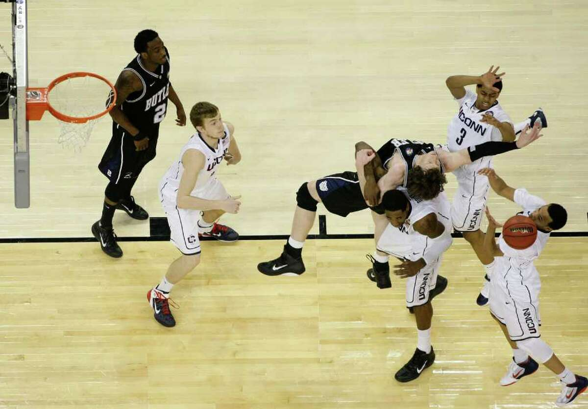 Butler forward Matt Howard (54) battles for the ball against Connecticut forward Jeremy Lamb (3), Connecticut center Alex Oriakhi (34), (bottom) and Connecticut guard Shabazz Napier (13) during the second half as UConn defeated Butler 53-41 during the NCAA National Championship at Reliant Stadium on Monday, April 4, 2011, in Houston. ( Nick de la Torre / Houston Chronicle )