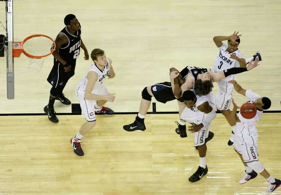 Butler forward Matt Howard (54) battles for the ball against Connecticut forward Jeremy Lamb (3), Connecticut center Alex Oriakhi (34), (bottom) and Connecticut guard Shabazz Napier (13) during the second half as UConn defeated Butler 53-41 during the NCAA National Championship at Reliant Stadium on Monday, April 4, 2011, in Houston.  ( Nick de la Torre / Houston Chronicle ) Photo: Nick De La Torre, Houston Chronicle For The Connecticut Post / Houston Chronicle for the Connecticut Post