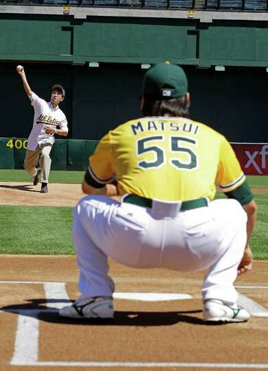 Kazuhiko Abe, left, CEO of Capcom USA, throws the ceremonial first pitch to Oakland Athletics' Hidek