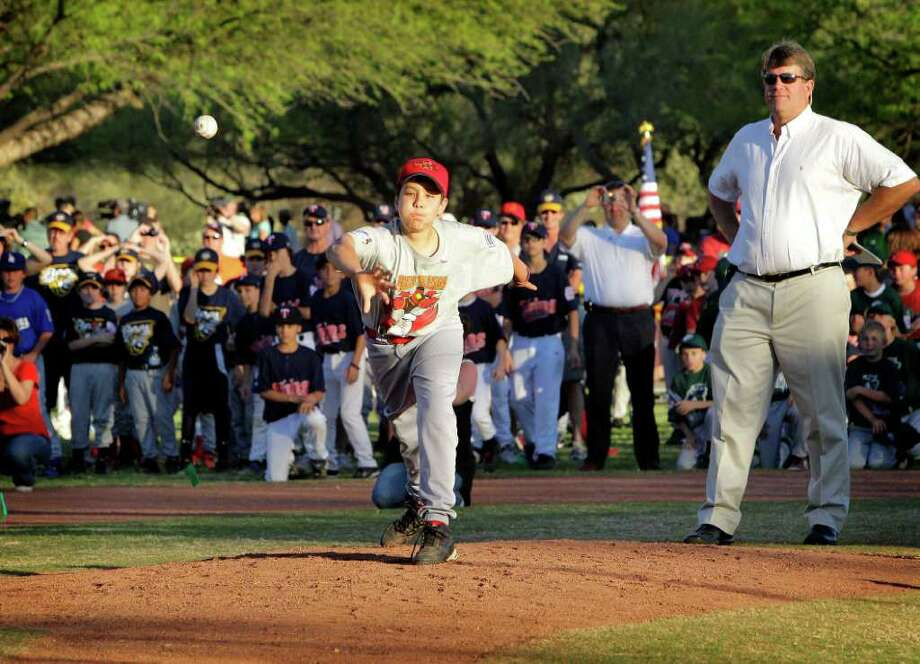 Dallas Green throws out the ceremonial first pitch as his dad, John Green looks on at opening night of the Canyon Del Oro little league, Friday, April 1, 2011, in Oro Valley, Ariz. A statue was unveiled and a field was renamed Green Field in memory of Green's sister, Christina-Tahylor Green who played little league for Canyon Del Oro. Christina-Taylor Green was fatally shot on Jan 8th while attending an event with Congresswoman Gabrielle Giffords. Photo: AP