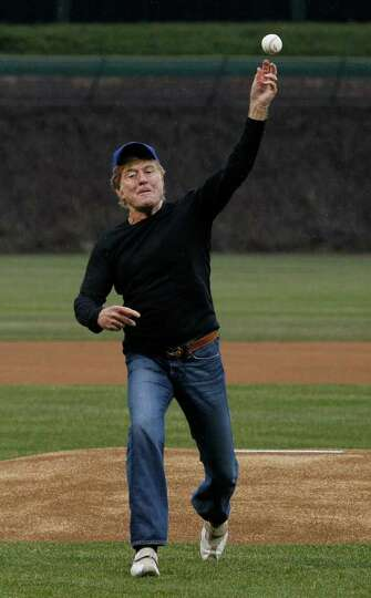 Actor Robert Redford throws out a ceremonial first pitch before the opening day baseball game betwee