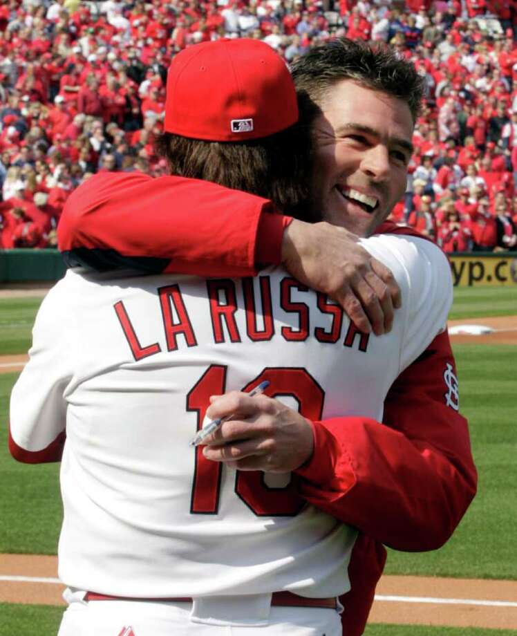 Former St. Louis Cardinals center fielder Jim Edmonds, right, hugs Cardinals manager Tony La Russa after throwing out the ceremonial first pitch before the start of a baseball game against the San Diego Padres on opening day Thursday, March 31, 2011, in St. Louis. Edmonds announced his retirement during spring training this year. Photo: AP