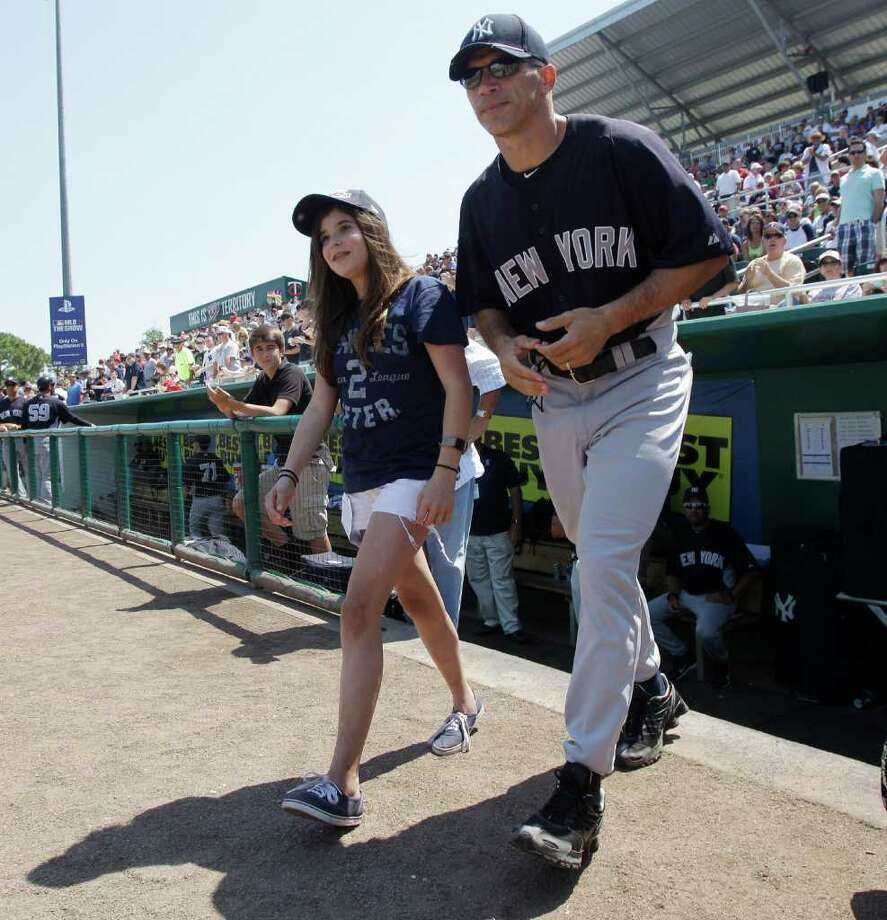 New York Yankees manager Joe Girardi walks onto the field with Julianne Ramirez, 12, of Tampa as she went out to throw the ceremonial first pitch before the Yankess face the Minnesota Twins in a spring training baseball game in Fort Myers, Fla., Sunday, March 27, 2011. Ramirez was honored by the Yankees after saving the life of a three-year-old, who nearly drowned at a pool party, by rescuing the toddler and administering CPR. Photo: AP