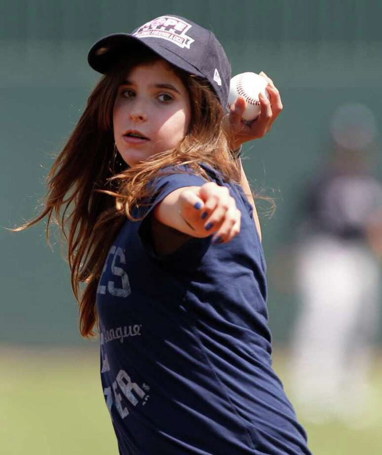 Julianne Ramirez, 12, of Tampa throws out the ceremonial first pitch before the New York Yankees face the Minnesota Twins in a spring training baseball game in Fort Myers, Fla., Sunday, March 27, 2011. Ramirez was honored by the Yankees after saving the life of a three-year-old, who nearly drowned at a pool party, by rescuing the toddler and administering CPR. Photo: AP