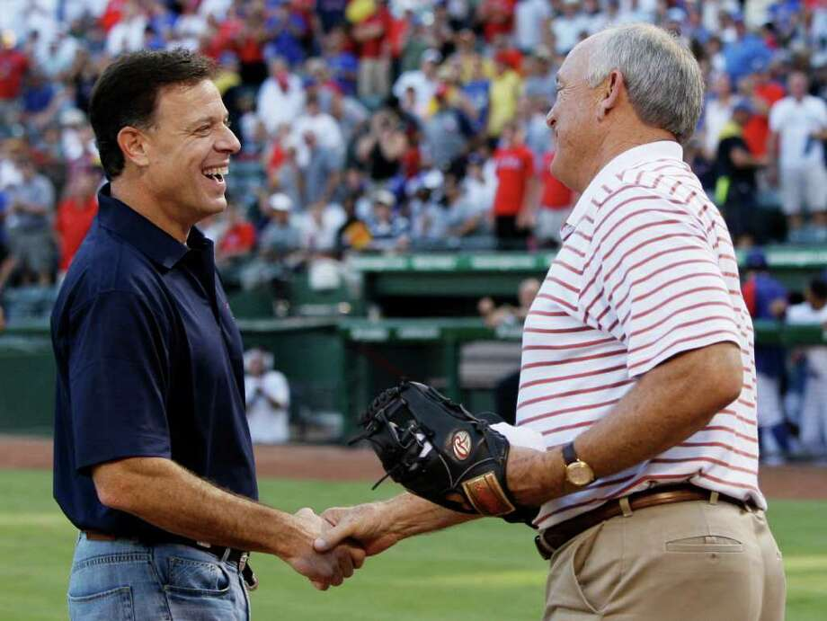 Texas Rangers co-owner Chuck Greenberg, left, shakes hands with team president and co-owner Nolan Ryan, right, after Greenberg threw the honorary first pitch to Ryan before a baseball game against the Boston Red Sox Saturday Aug. 14, 2010, in Arlington, Texas. Photo: AP
