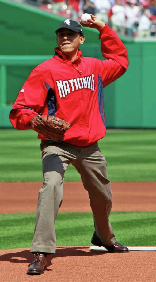 Wearing a Washington Nationals jacket and a Chicago White Sox hat, President Barack Obama delivers the first pitch of the Washington Nationals home opening baseball game against the Philadelphia Phillies, Monday, April 5, 2010, at Nationals Park in Washington. Photo: Alex Brandon, AP / AP