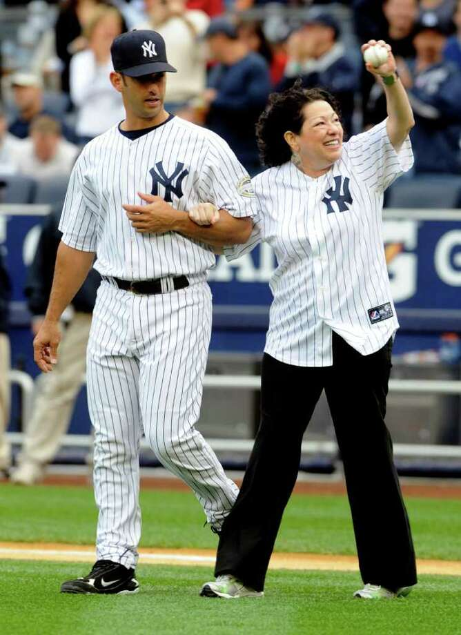 Supreme Court Justice Sonia Sotomayor, right, a New York Yankees fan from the Bronx, New York, is escorted to the pitching mound by New York Yankees' Jorge Posada before  throwing out the ceremonial first pitch before the Yankees played the Boston Red Sox in their baseball game at Yankee Stadium in New York, Saturday, Sept. 26, 2009. Photo: Henny Ray Abrams, AP / FR151332 AP