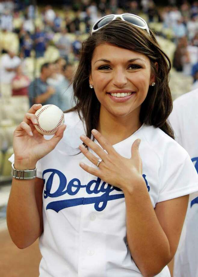 "DeAnna Pappas from ABC's ""The Bachelorette"" television reality shows her engagement ring and the baseball that she threw for the first pitch  before the start of the baseball game between the Florida Marlins and the Los Angeles Dodgers at Dodger Stadium  in Los Angeles, Thursday, July 10, 2008. Photo: Kevork Djansezian, AP / AP"