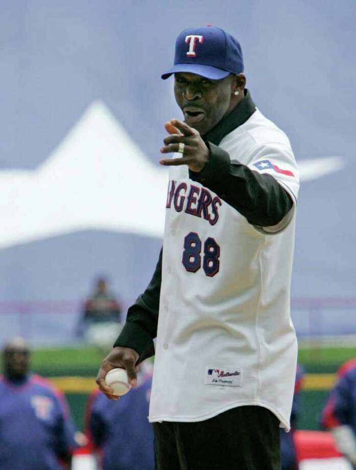 NFL Hall of Famer Michael Irvin points to home plate as he prepares to throw out the ceremonial first pitch at the Texas Rangers home-opener baseball game against the Boston Red Sox in Arlington, Texas, Friday, April 6, 2007. The Rangers won 2-0. Photo: Tony Gutierrez, AP / AP