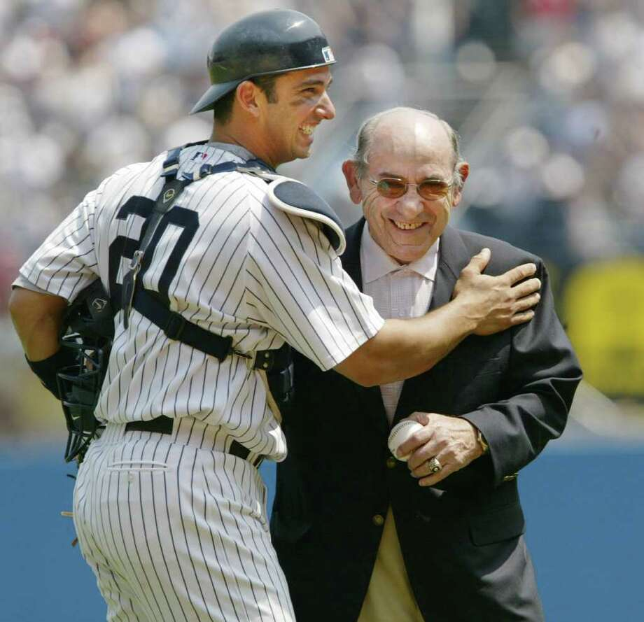 New York Yankees catcher Jorge Posada, left, congratulates former Yankees catcher Yogi Berra after Berra threw out the ceremonial first pitch in the Yankees game against the Seattle Mariners, Wednesday, May 11, 2005, at Yankee Stadium in New York.  Berra will turn 80-years old on Thursday. Photo: KATHY WILLENS, AP / AP