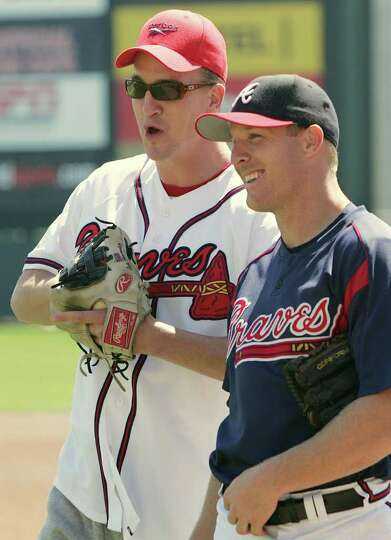 Indianapolis Colts quarterback Peyton Manning, left, talks with Atlanta Braves' Pete Orr, right, bef