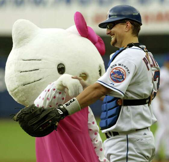 New York Mets catcher Jason Phiilips interacts with Hello Kitty who threw out the first pitch in the