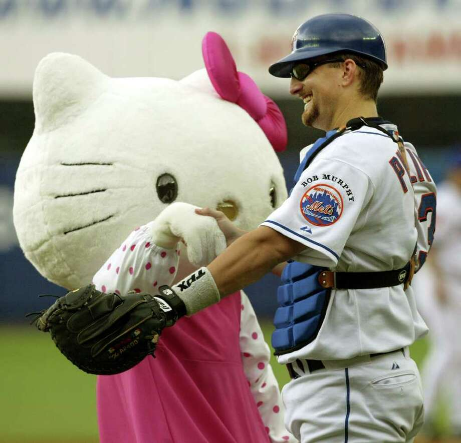 New York Mets catcher Jason Phiilips interacts with Hello Kitty who threw out the first pitch in the Mets' 2-0 loss to the Arizona Diamondbacks, Sunday, Aug. 15, 2004, at Shea Stadium in New York. Photo: KATHY WILLENS, AP / AP