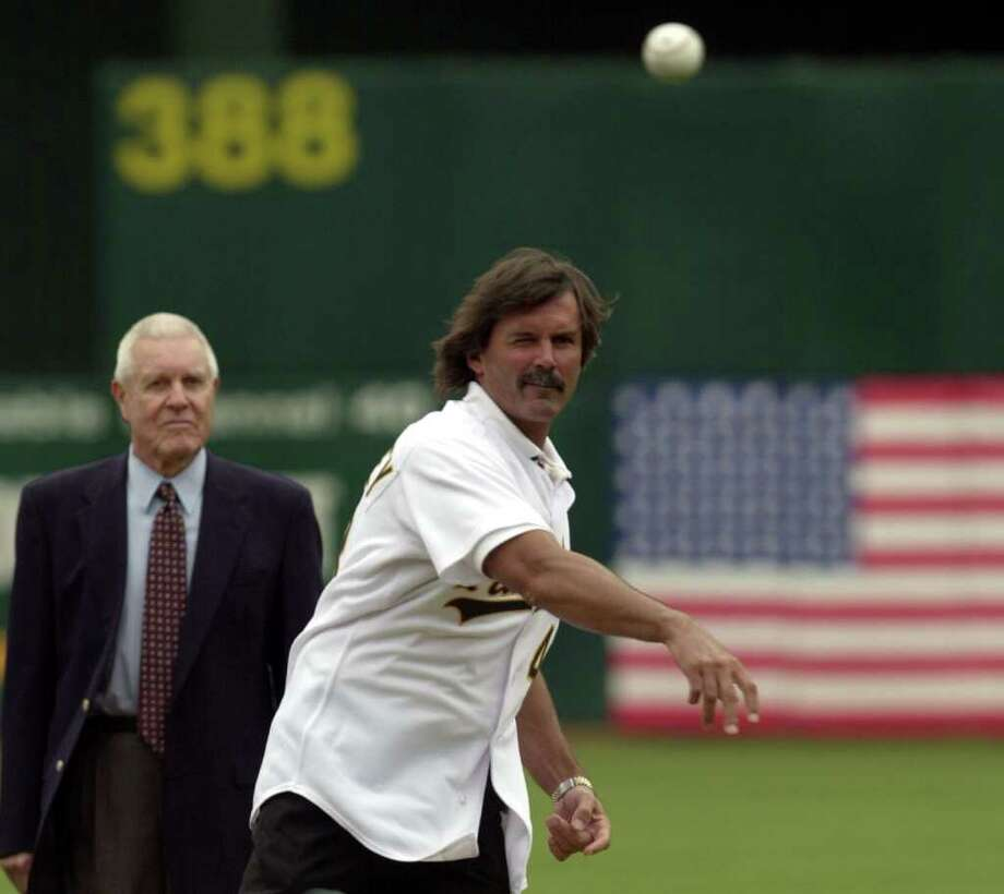 Former Oakland Athletics pitcher Dennis Eckersley throws the game's first pitch as broadcaster Lon Simmons, left, watches before the start of a game against the Kansas City Royals, Saturday, Aug. 14, 2004, in Oakland, Calif. Eckersley and Simmons were inducted last month into the Baseball Hall of Fame. Photo: MARCIO JOSE SANCHEZ, AP / AP