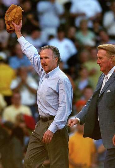Boston real estate developer and Los Angeles Dodgers owner Frank McCourt lifts his glove in the air