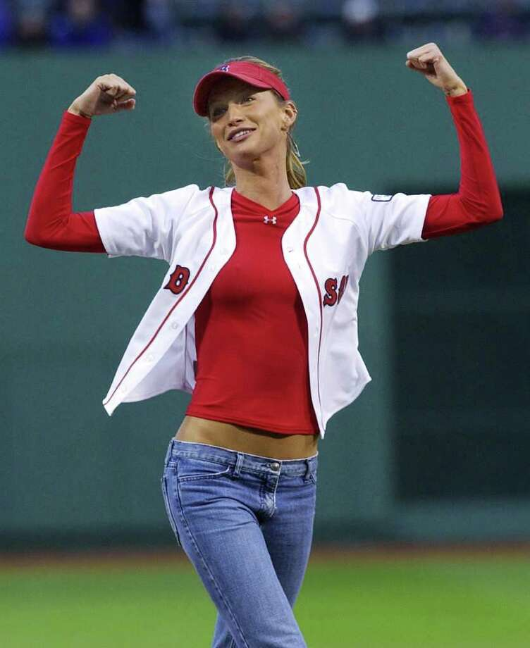 Supermodel Gisele Bundchen of Brazil gestures that she is strong after throwing the ceremonial first pitch over the catcher's head prior to the game between the Oakland Athletics and the Boston Red Sox at Fenway Park in Boston Tuesday, May 25, 2004. Photo: ELISE AMENDOLA, AP / AP