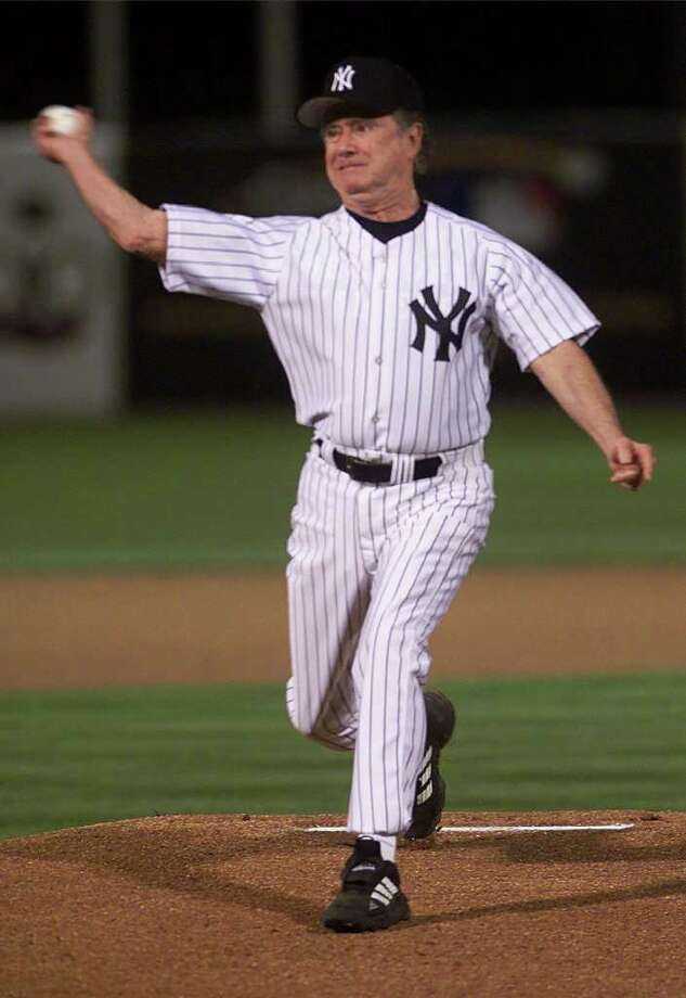 """Who Wants To Be A Millionaire"" host Regis Philbin tosses out the first pitch of the New York Yankees and Minnesota Twins game, Tuesday, March 7, 2000, at Legends Field in Tampa, Fla. Photo: SUZANNE PLUNKETT, AP / AP"