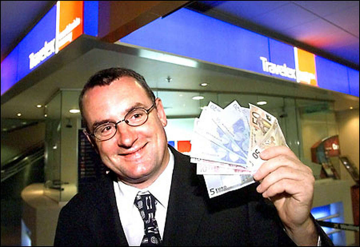 Trevor Mallard, New Zealand's associate minister of finance, displays the 225 euros he bought at a currency exchange at Wellington International Airport early today.