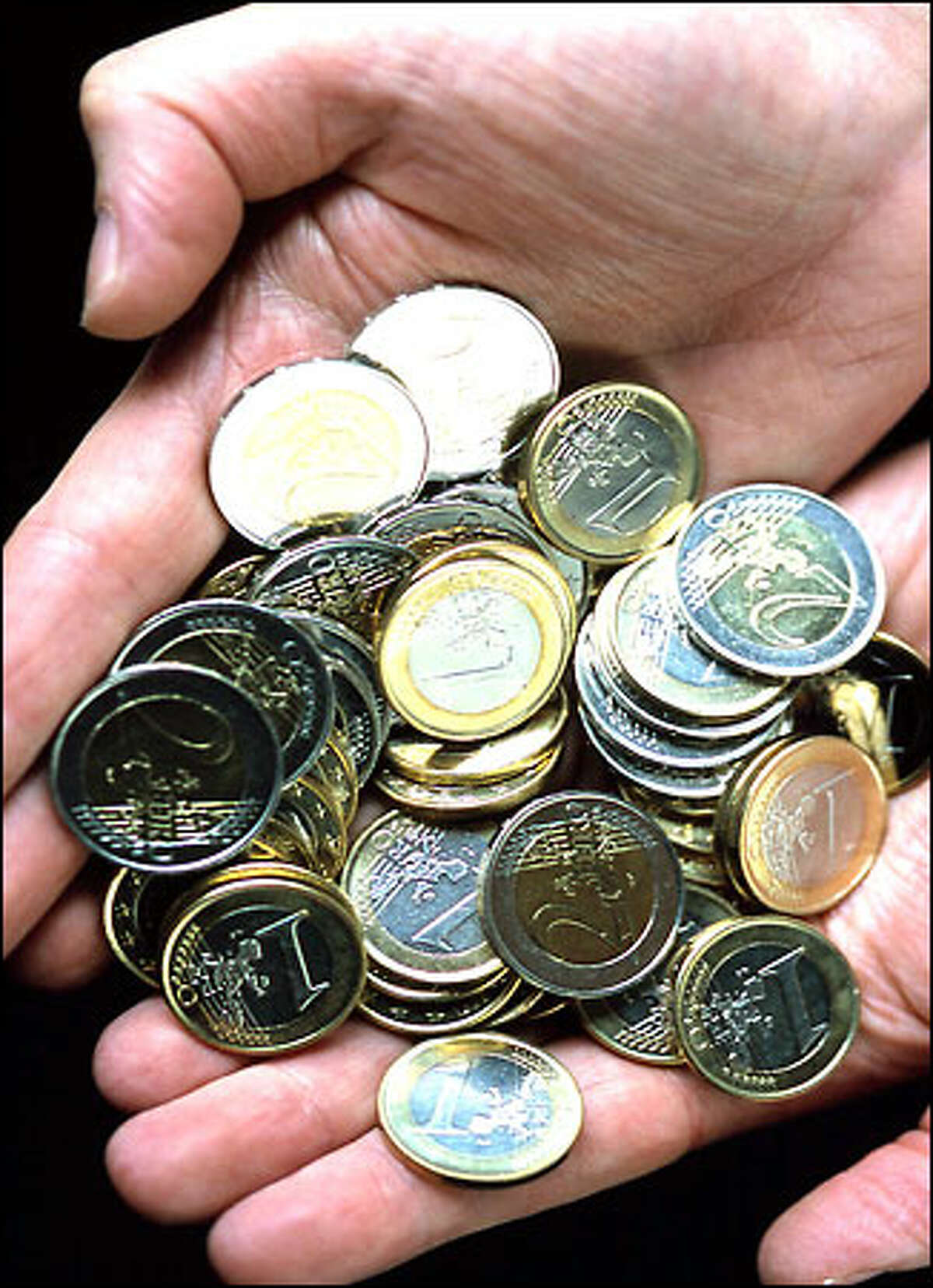 One-euro and 2-euro coins like these are the new money of millions.