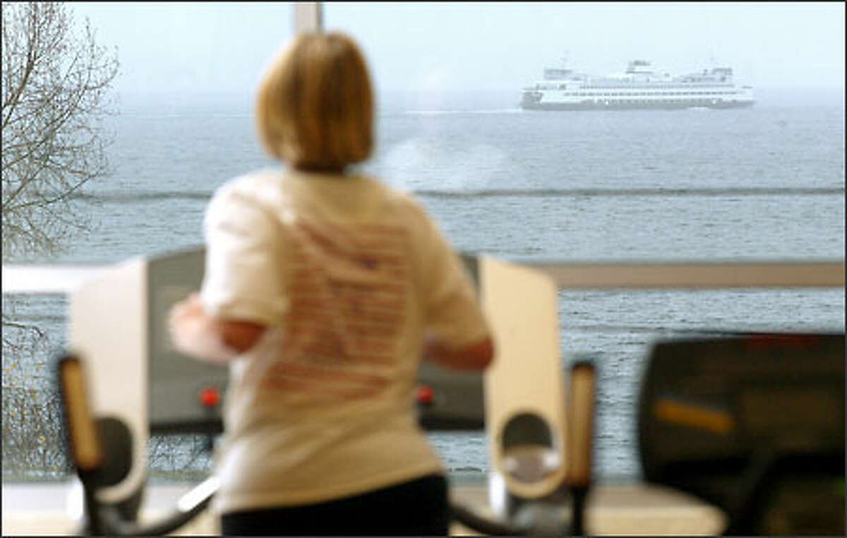 A ferry glides through Elliott Bay as Kim Yates of Seattle works out on a running machine at Rain Fitness. Yates lost 115 pounds last year and joined the club in November to keep the weight off.
