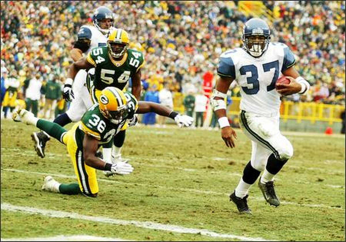Shaun Alexander strides into the end zone past a diving Nick Collins. It was Alexander's record-setting 28th touchdown of the season.