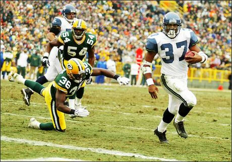 Shaun Alexander strides into the end zone past a diving Nick Collins. It was Alexander's record-setting 28th touchdown of the season. Photo: Scott Eklund, Seattle Post-Intelligencer / Seattle Post-Intelligencer