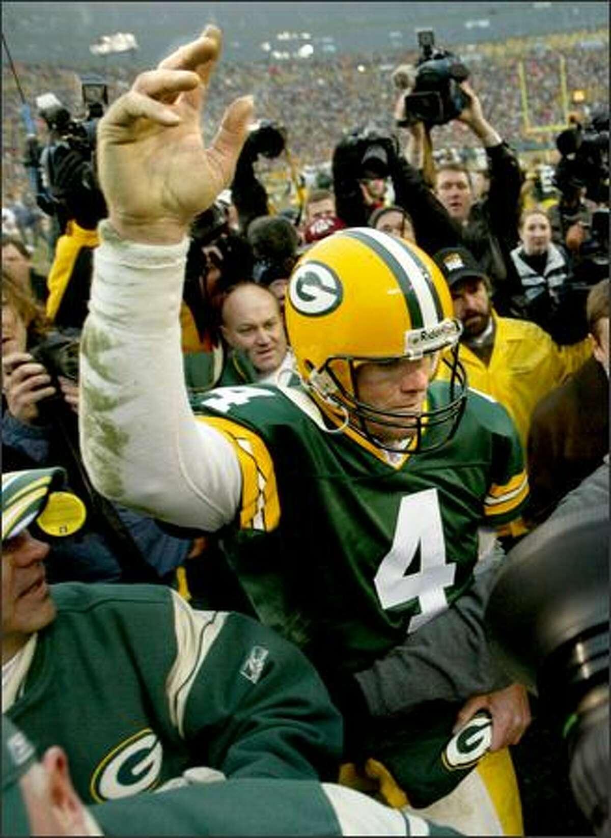 Packers quarterback Brett Favre waves to the fans as he walks off the field.