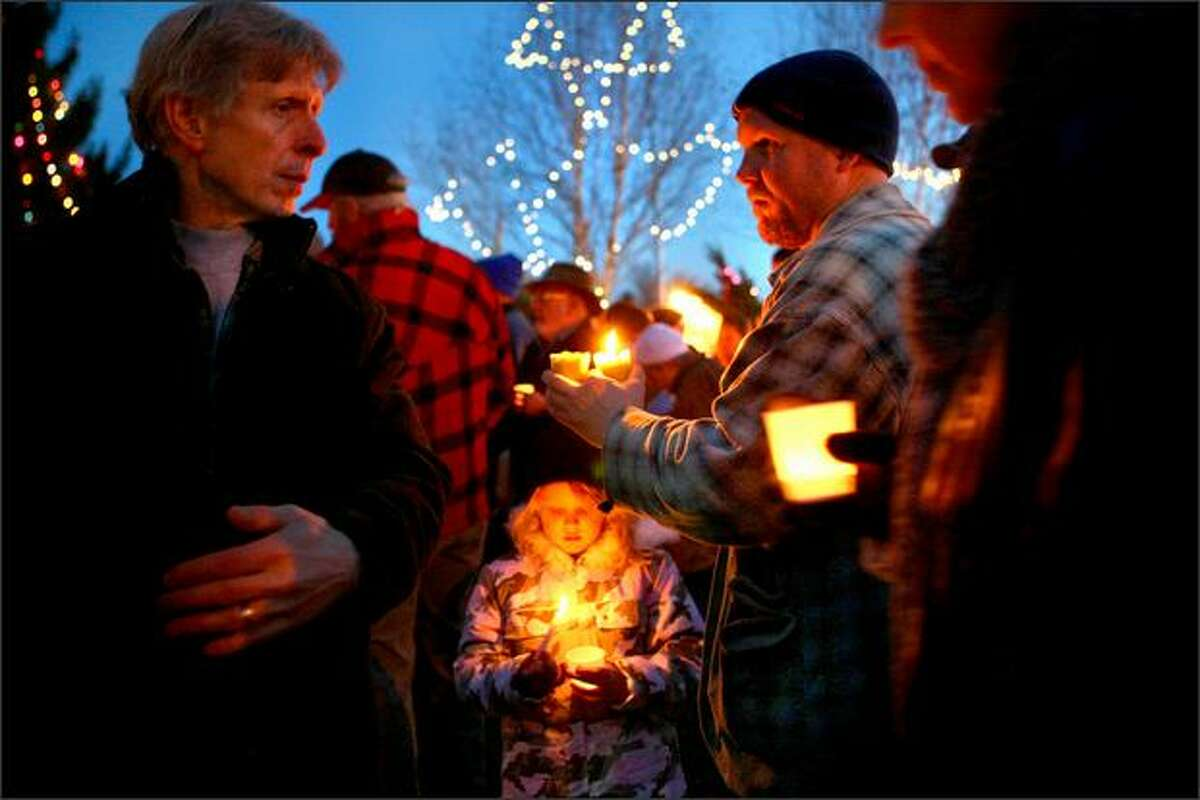 Six-year-old Elliott, center, and her father, John, right, gather with other local residents at Tolt Town Commons in Carnation.