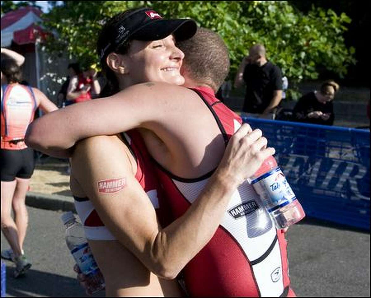 Terresa Nelson (cq), who took first with a time of 1:08:11 in the female division, left, hugs her boyfriend Mark Webb after he