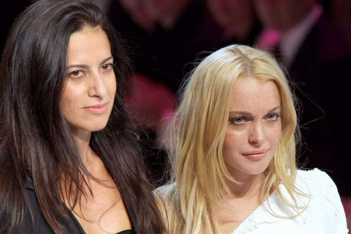 Spanish designer Estrella Arch (left) and U.S. actress Lindsay Lohan, appointed as artistic advisor, acknowledge the public at the end of the Emanuel Ungaro ready-to-wear Spring-Summer 2010 fashion show on October 4, 2009 in Paris.