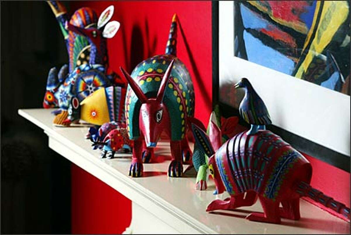 Carved armadillos from Oaxaca are grouped on a mantel in Barrientos' home. Buying that first piece of Mexican folk art can lead to the plunge into bright wall colors, says store owner Heather Stockdale.