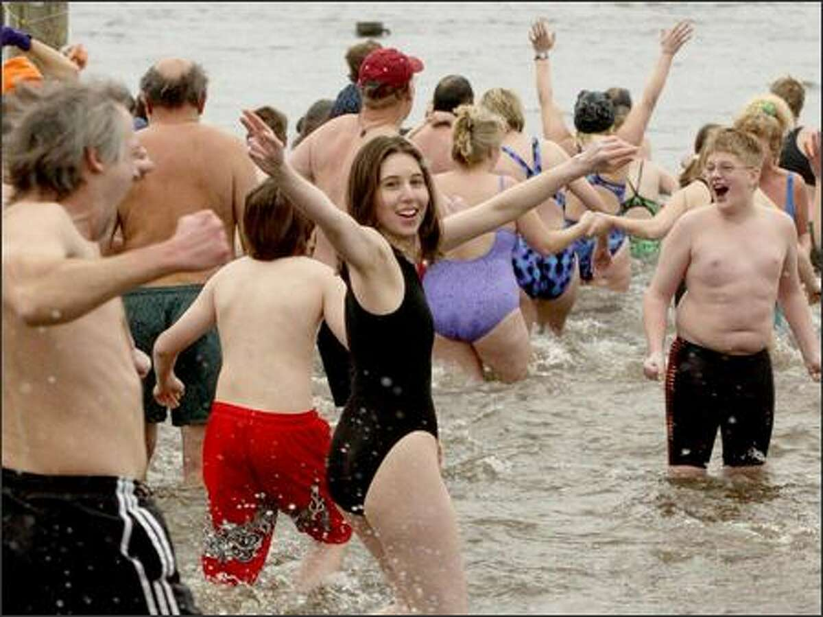 Dawn Nicks, 28, of Bellevue waves at her boyfriend, Kevin Connolly, as she trots into the 42-degree waters of Lake Washington yesterday. Nicks and 350 other people welcomed the New Year by taking part in the second annual Polar Bear Swim at Matthews Beach. For most, the cold dash and dip lasted just a few seconds.