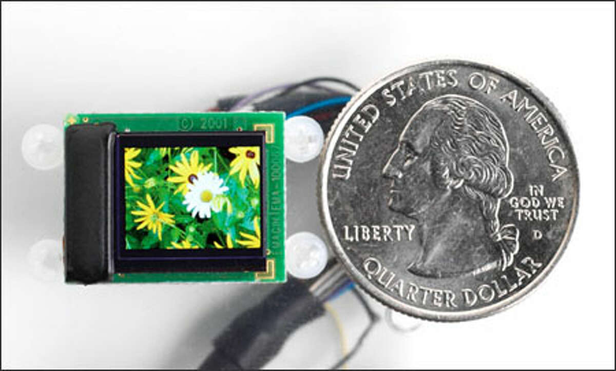 A close-up of the display component of the new wearable display for video iPods by eMagin Corp., compared with the size of a quarter.