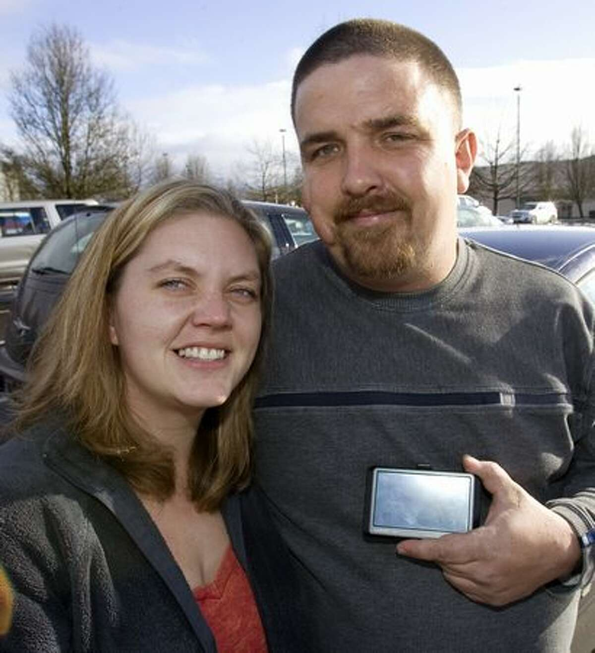 Jeramie Griffin, right, holds his GPS unit while posing for a photo with girlfriend Megan Garrison in Wilsonville, Ore., on Dec. 30, 2009. The couple and their toddler got stuck on a backcountry road for 12 hours after following GPS instructions and became so distraught that they recorded a final goodbye on their video camera. GPS is no substitute for common sense, say law enforcement officials who have rescued three parties of holiday travelers in rural Oregon.(AP Photo/Don Ryan)