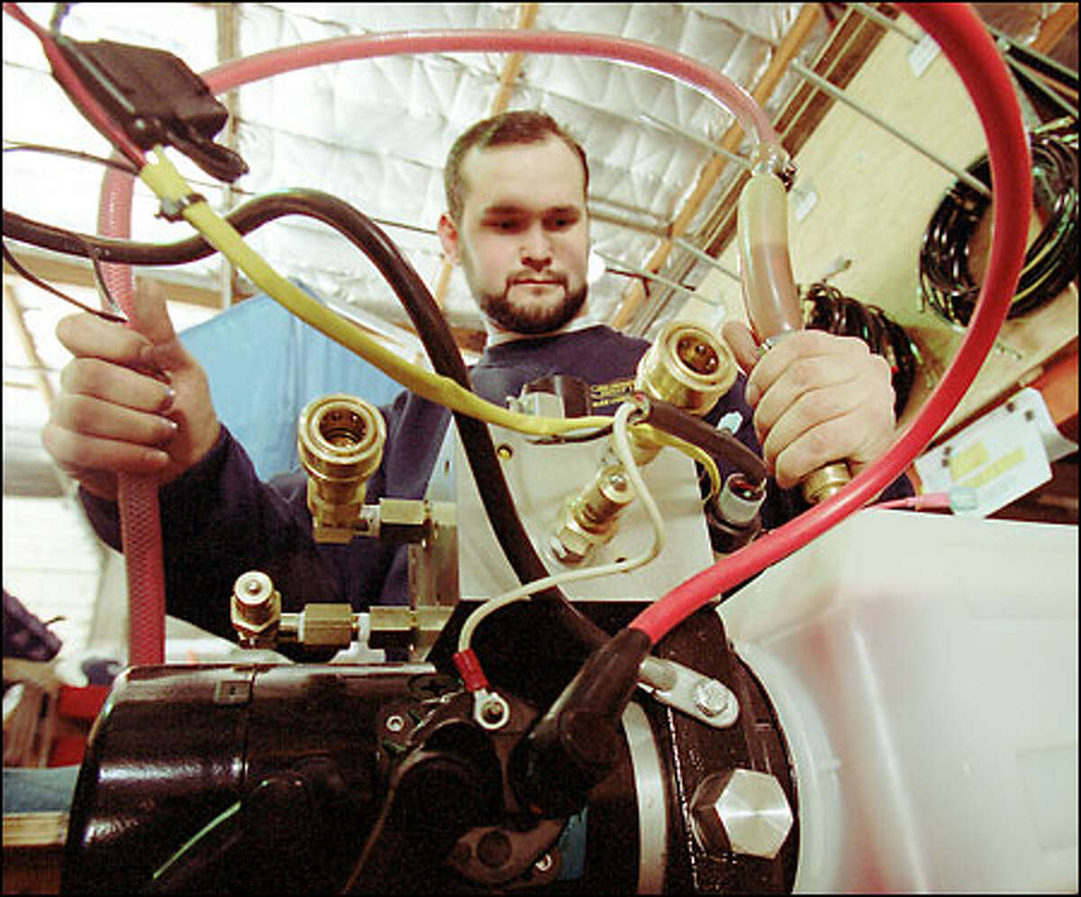 Worker Vladimir Filatov puts hoses on a power pack for a boat lift at Sunstream Corp. in Kent. Twenty people are employed building the lifts.