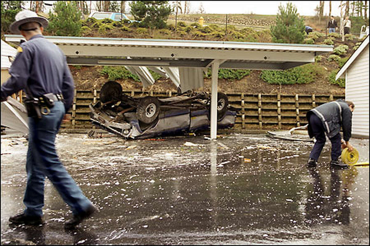A Washington state trooper walks past a stolen truck as a Bellevue firefighter rolls up a fire hose. The truck and two occupants crashed into an apartment carport on Cougar Mountain after leading troopers on a chase.