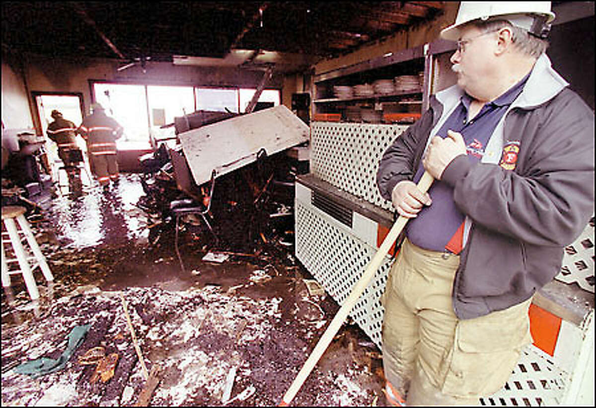 Lead Fire Investigator Gene Williams of the Tacoma Fire Department pauses inside the Rite Spot Cafe, which was gutted by fire Tuesday night.