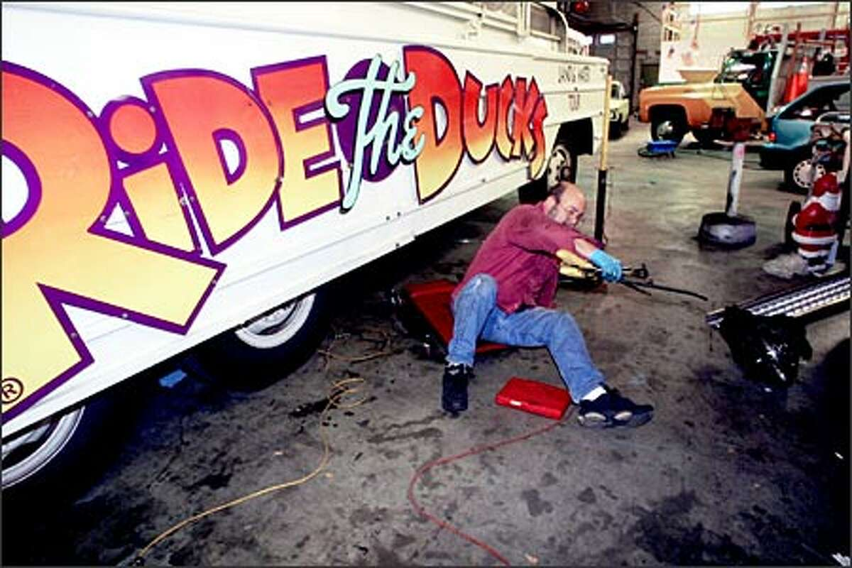"""Marty Peterson finishes repairs on one of the Ride the Ducks vehicles that will be used during downtown Seattle's """"Smooth Sale-ing"""" promotion."""