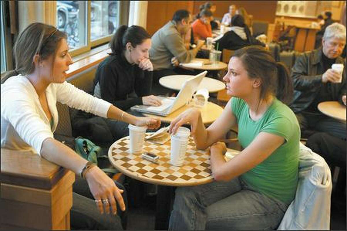 Kate Garberich, left, and Jane Corcoran, who visit a Starbucks almost every day, chat Tuesday at the Starbucks at University Village.