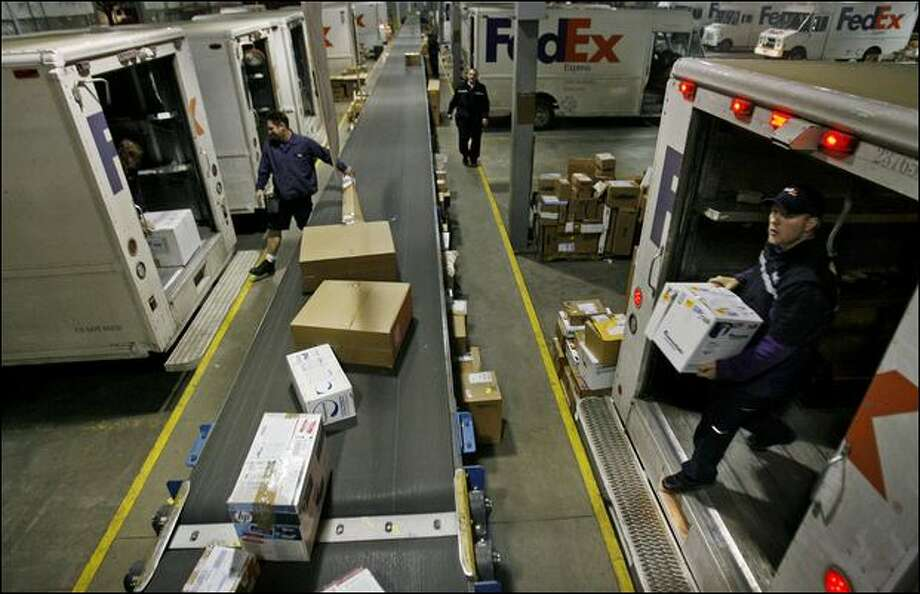 Couriers including Matt Klein, right, unload outbound freight Friday for FedEx in Seattle, which expects to clear out its backlog by today. Photo: Dan DeLong, Seattle Post-Intelligencer / Seattle Post-Intelligencer