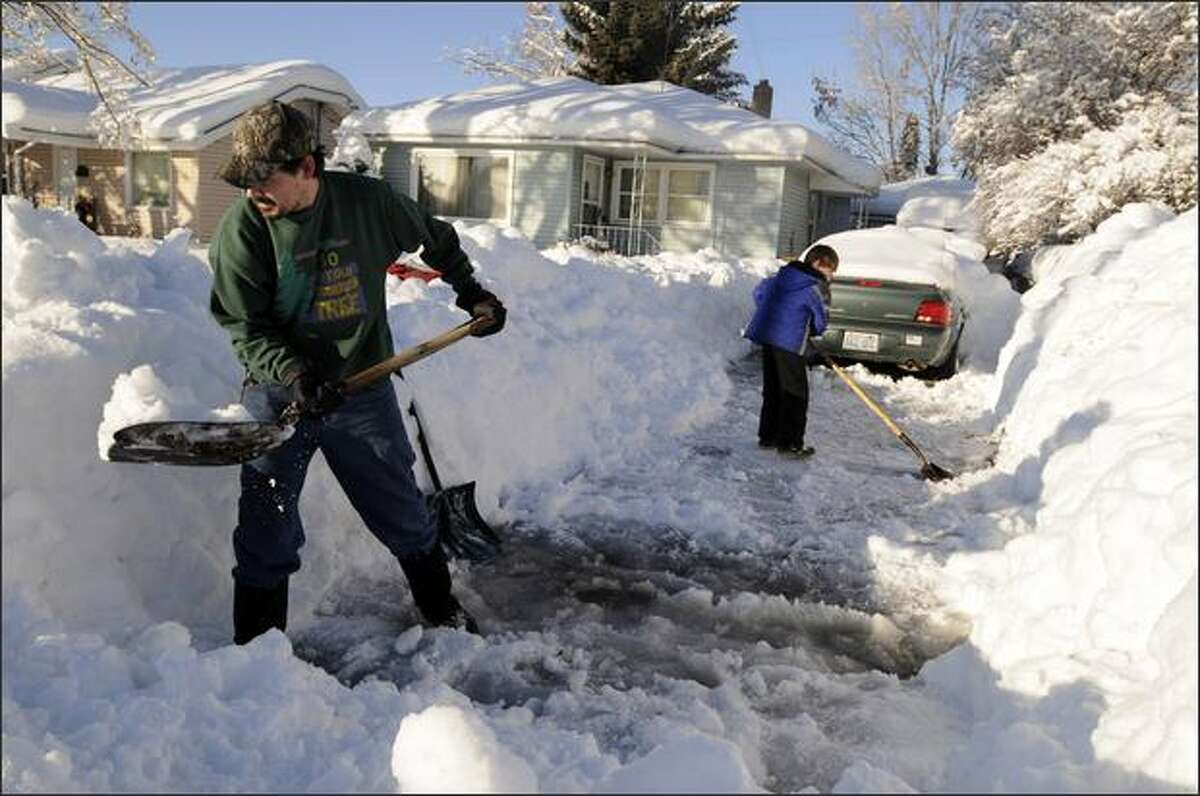 Kevin Newman, left, a Cubmaster for a pack of Cub Scouts, digs out a driveway on the north side of Spokane with his son, Kaden, right, age 7, as a service project with the local Boy Scout community on Friday. More snow is forecast for storm-weary Spokane.