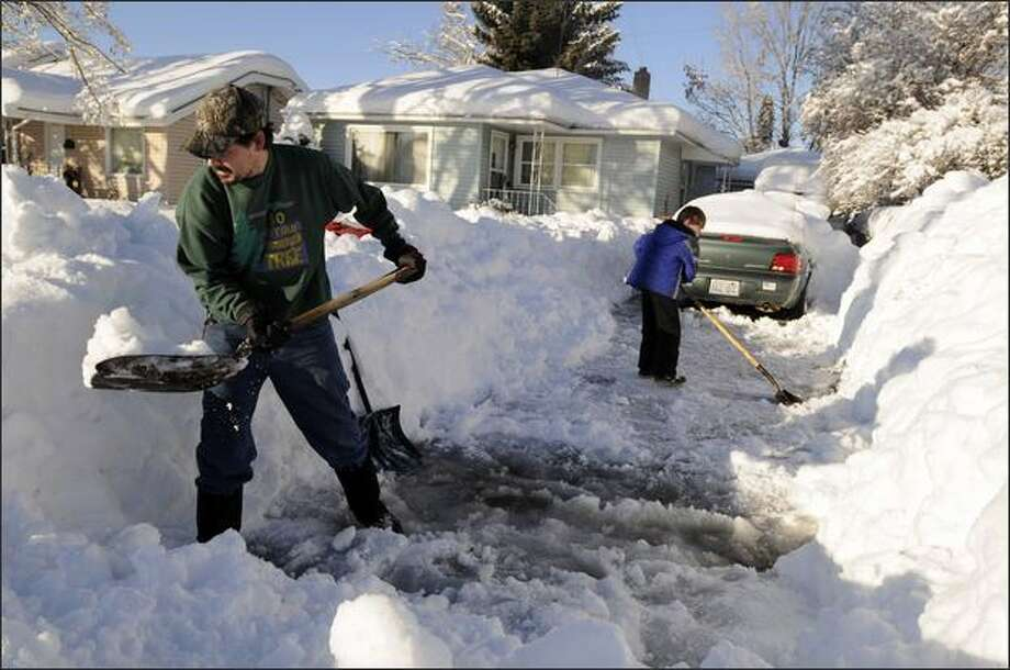 Kevin Newman, left, a Cubmaster for a pack of Cub Scouts, digs out a driveway on the north side of Spokane with his son, Kaden, right, age 7, as a service project with the local Boy Scout community on Friday. More snow is forecast for storm-weary Spokane. Photo: Associated Press / Associated Press
