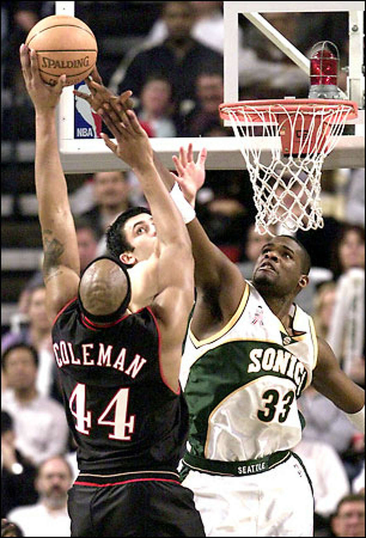 Philadelphia's Derrick Coleman shots a basket over Jerome James (33) and Vladimir Radmanovic.