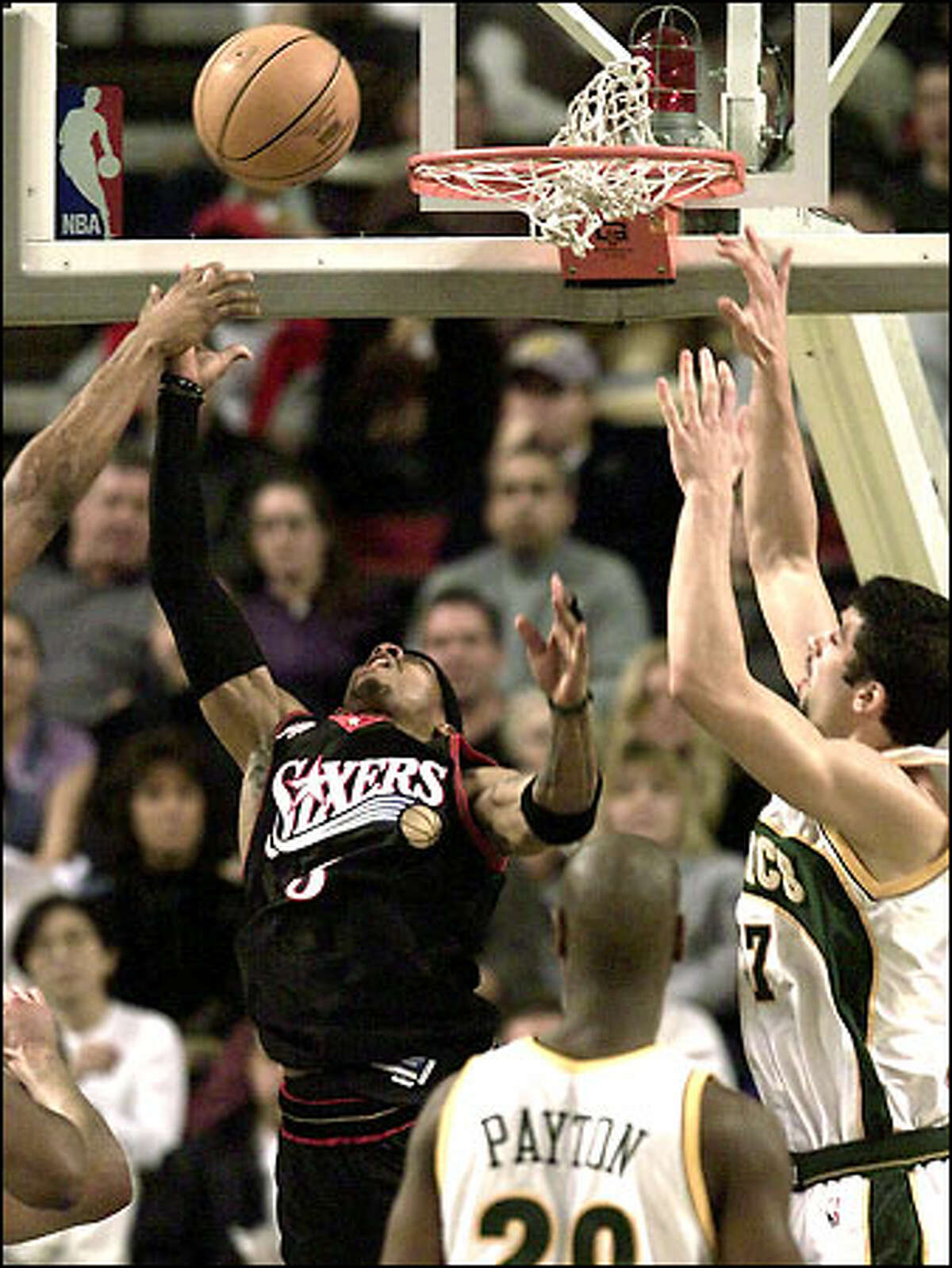 The 76ers' Allen Iverson underhands a ball to the basket in the first half as Vladimir Radmanovic tries to block the shot. Gary Payton looks on.